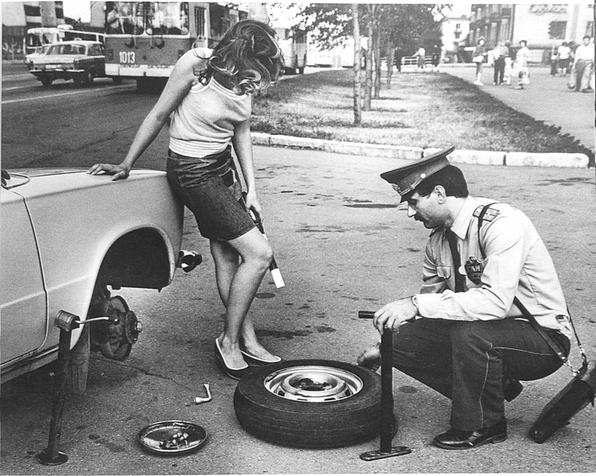 The employee of GAI helps the girl with replacement of a wheel, the USSR, the 1980th.